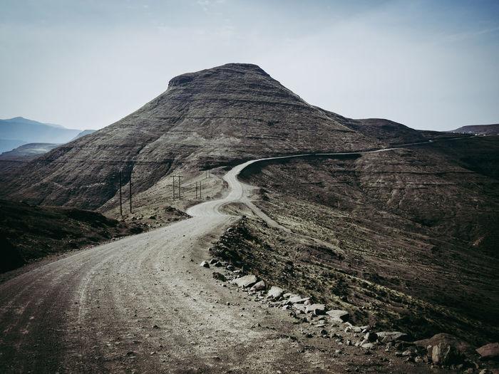 Dangerous Dirt Road Leading Towards Mountain Against Sky In Arid Landscape Of Lesotho, Africa