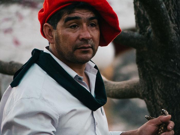 Thoughtful man wearing flat cap against tree trunk
