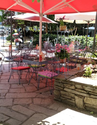 Chairs and tables at sidewalk cafe against building