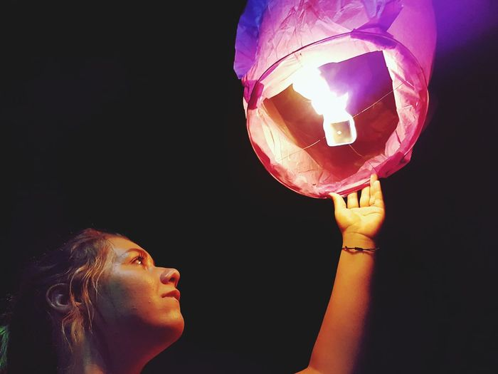 Low angle view of woman releasing paper lantern in sky