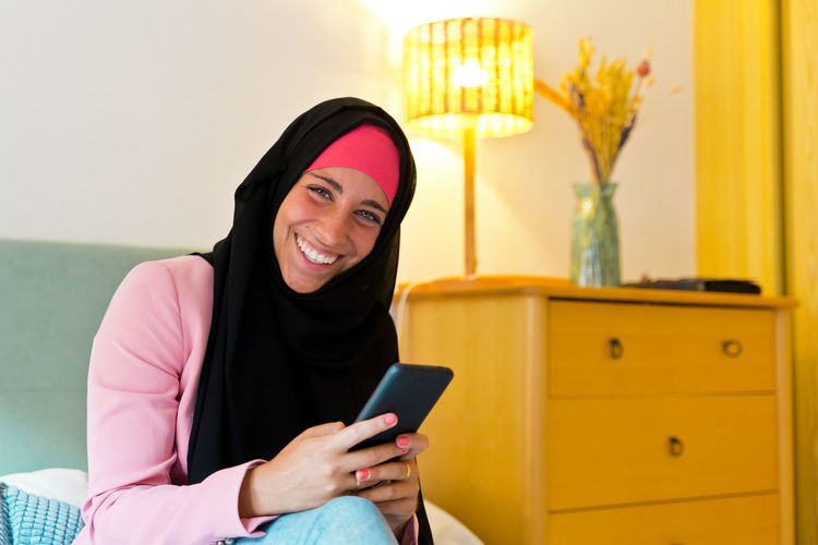Young woman using mobile phone while sitting on laptop
