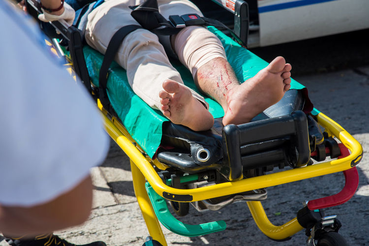 Paramedic Accident Day Help Human Foot Land Vehicle Leisure Activity Lifestyles Low Section Lying Down Men Mode Of Transportation Nature Outdoors Real People Rescuer Safety Sunlight Transportation Travel