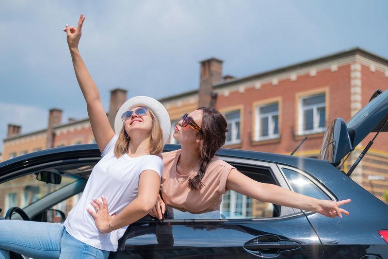 Cheerful female friends enjoying by car