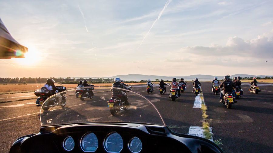 Rear view of bikers on runway