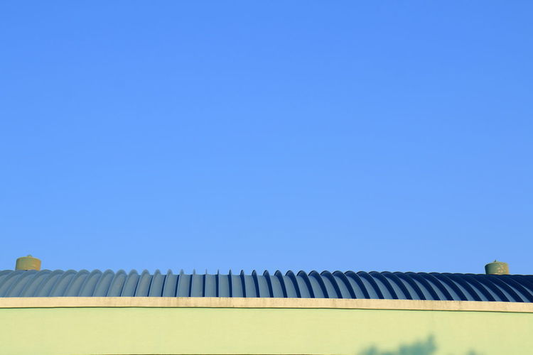 Low angle view building roof against blue sky