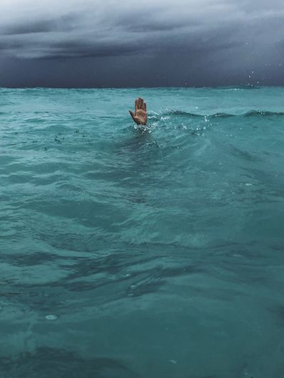 Cropped hand of person sinking in sea against sky