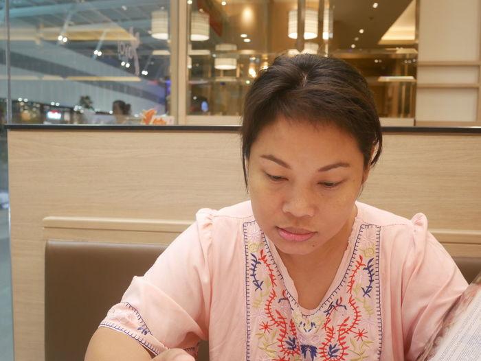 Mid adult woman reading menu in restaurant
