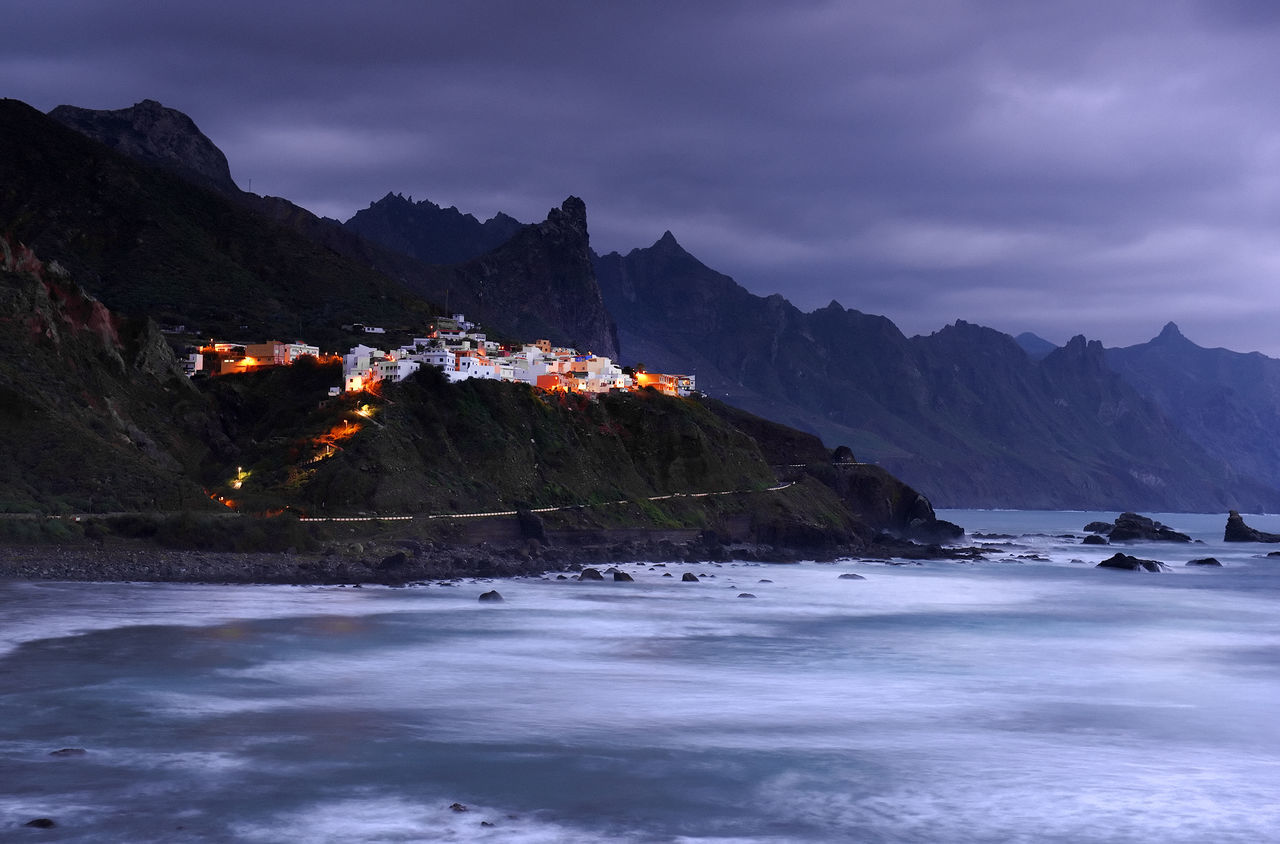 Mountains By Sea Against Cloudy Sky During Sunset