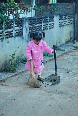 Children work sweep the floor Pink Color One Person Lifestyles Outdoors Day Children Girl Working Sweeping Broom Swab Floor