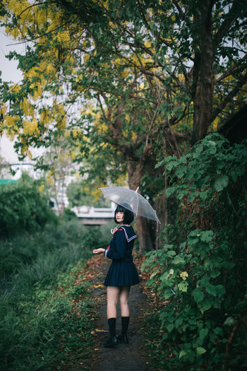 Full length of woman holding umbrella while standing on footpath in forest