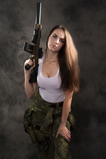 Aggression  Beautiful Woman Beauty Casual Clothing Clothing Gun Hair Hairstyle Holding Long Hair Looking At Camera One Person Portrait Real People Standing Three Quarter Length Weapon Women Young Adult Young Women