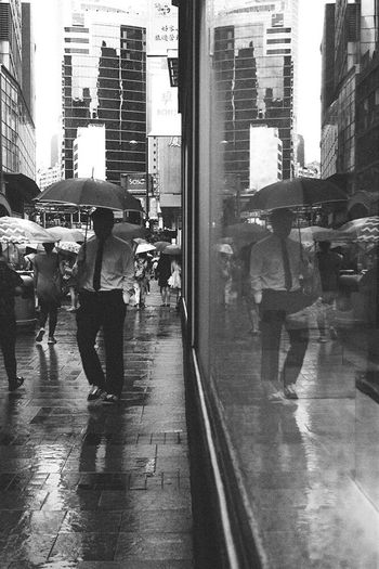 People walking on wet street in city
