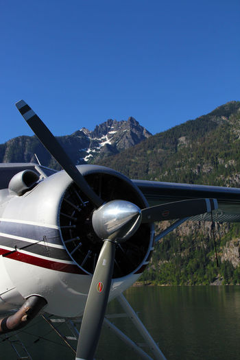 Seaplane Over Lake By Mountains Against Sky