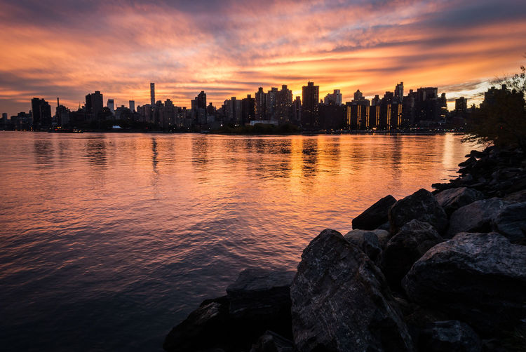 Scenic View Of Lake And Cityscape During Sunset