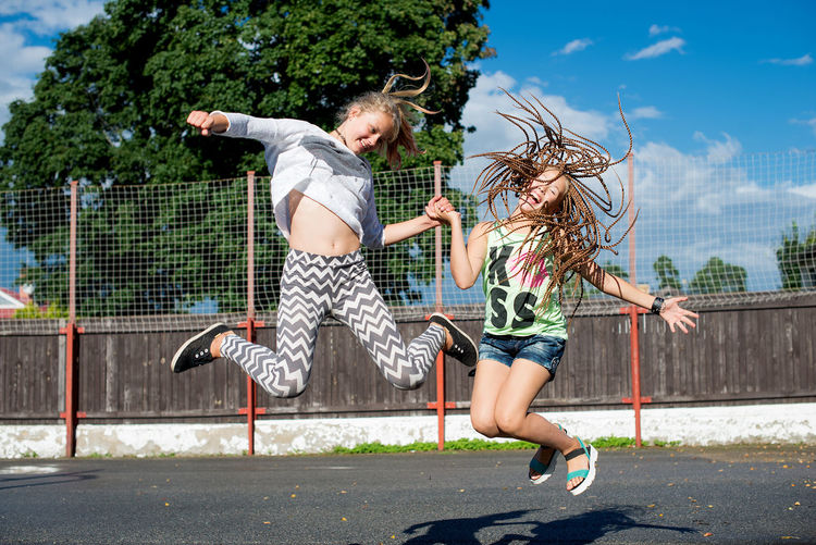 School Childrens Blond Hair Childhood Court Day Enjoyment Friendship Full Length Fun Girl Friend Girls Happiness Jumping Leisure Activity Lifestyles Mid-air Motion Outdoors People Real People Sky Teenager Togetherness Two People Vitality Fashion Stories