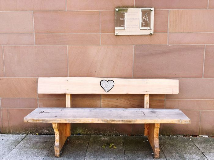 Empty bench on table against brick wall