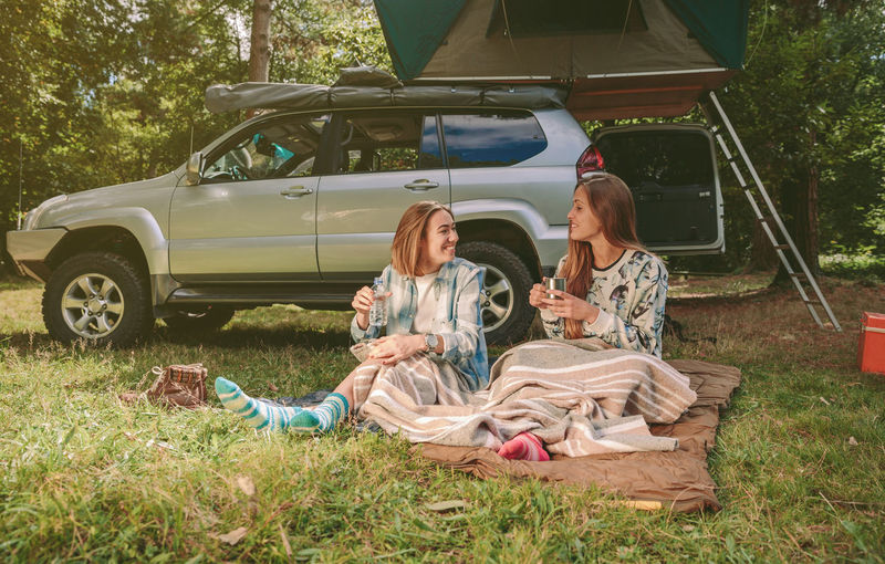 Happy young women friends resting sitting under a blanket in campsite into the forest Camping Campsite Coffee Hiking Horizontal Nature Travel Trip Woman Adventure Backpack Car Caucasian Cup Equipment Female Forest Mountain Off Road Outdoors Sleeping Bag Tent Two People Vehicle Young Adult