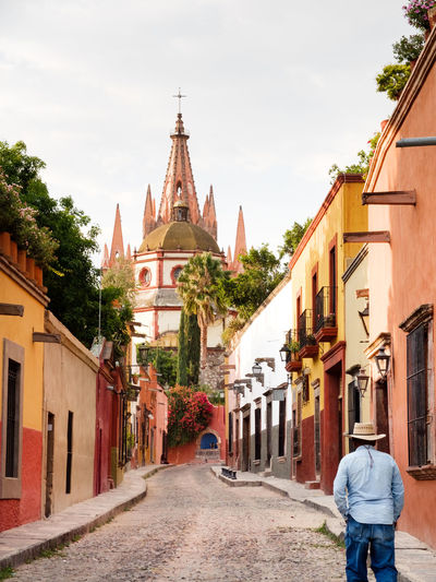 Rear View Of Man Walking On Footpath Amidst Buildings Against La Parroquia