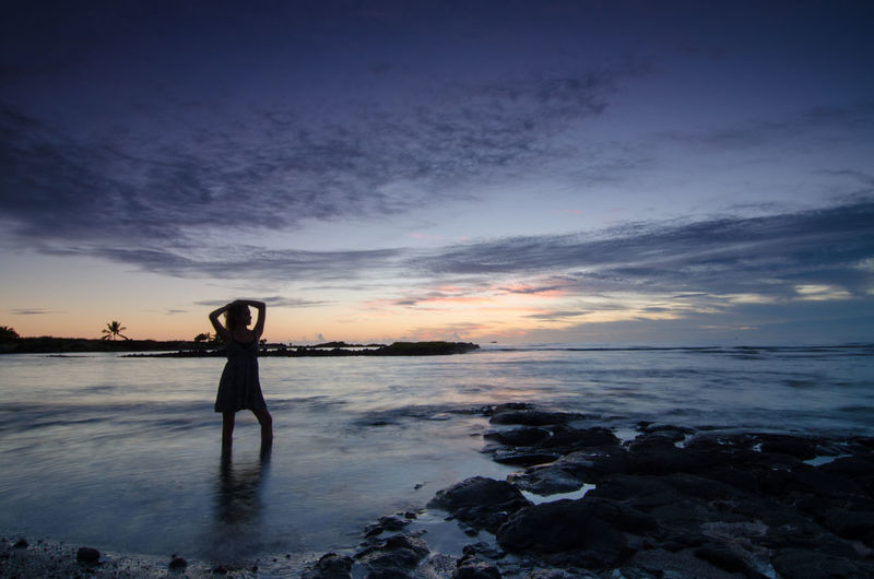 Silhouette Woman Standing On Sea Shore Against Sky At Dusk