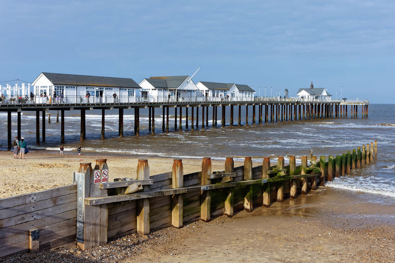 Pier on beach by sea against sky