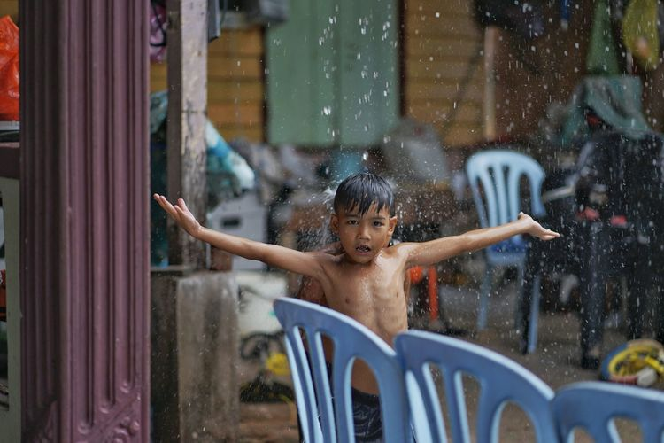 Portrait of boy with arms raised on rainy day