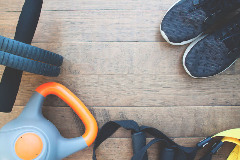 Fitness accessories on wooden background with copy space Body & Fitness Exercise Lifestyle TRX Trainer Active Activity Connection Equipment Fitness Gym Health Healthy High Angle View Kettlebell  Muscle Muscular Build No People Shoes Sneakers Sport Still Life Training Wood - Material Workout