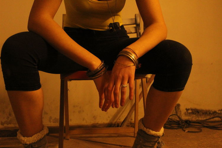 Midsection of woman sitting on chair against wall