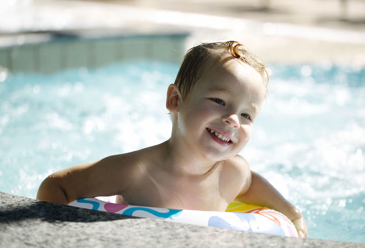 Happy boy with inflatable ring in swimming pool on sunny day