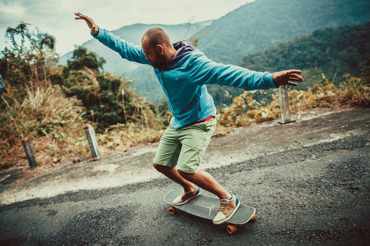 Mid Adult Man With Arms Outstretched Skateboarding On Road