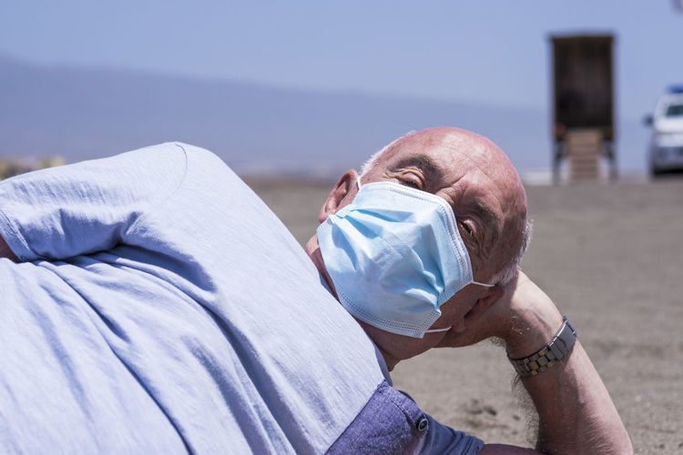 Portrait of senior man wearing flu mask relaxing on beach against sky