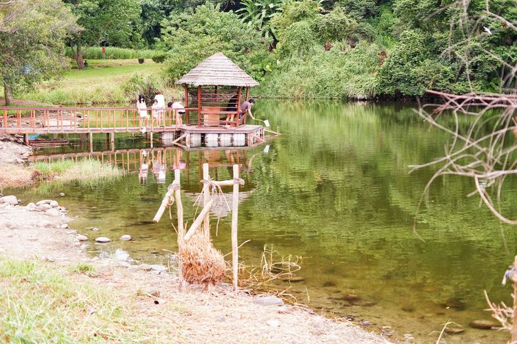 Built structure in lake with trees in foreground