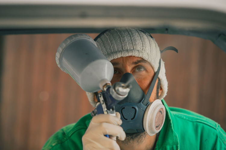 Close-up of man painting while wearing gas mask
