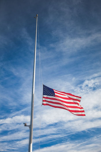 American flag flying at half staff to honor fallen soldiers American American Flag Mourning Respect Blue Cloud - Sky Day Emotion Flag Flagpole Flags Flying Half Staff Honor Low Angle View Motion National Icon No People Outdoors Patriotism Sky Striped Symbolic  Wind Windy