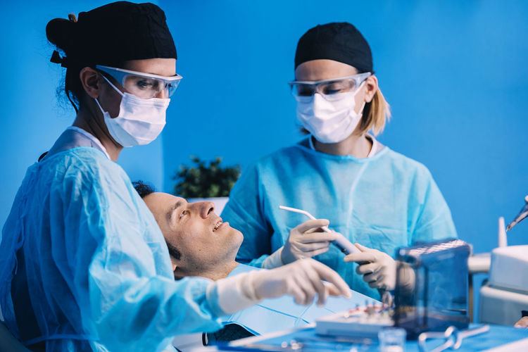 Dentists operating patient in medical clinic