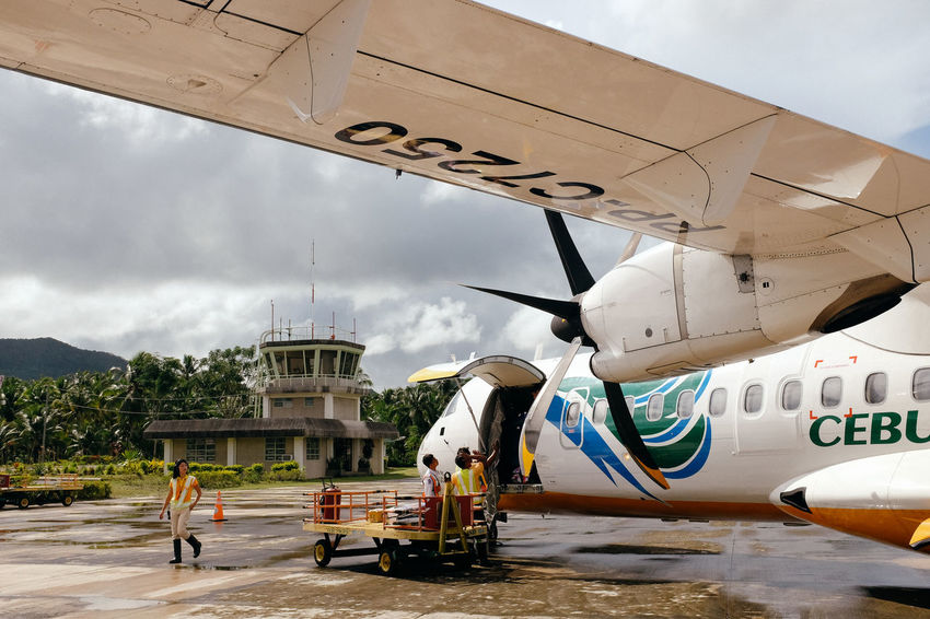 Airplane boarding in the jungle airport Aerospace Industry Air Vehicle Airplane Cloud - Sky Day Mode Of Transport Outdoors Passenger Boarding Bridge People Sky Transportation
