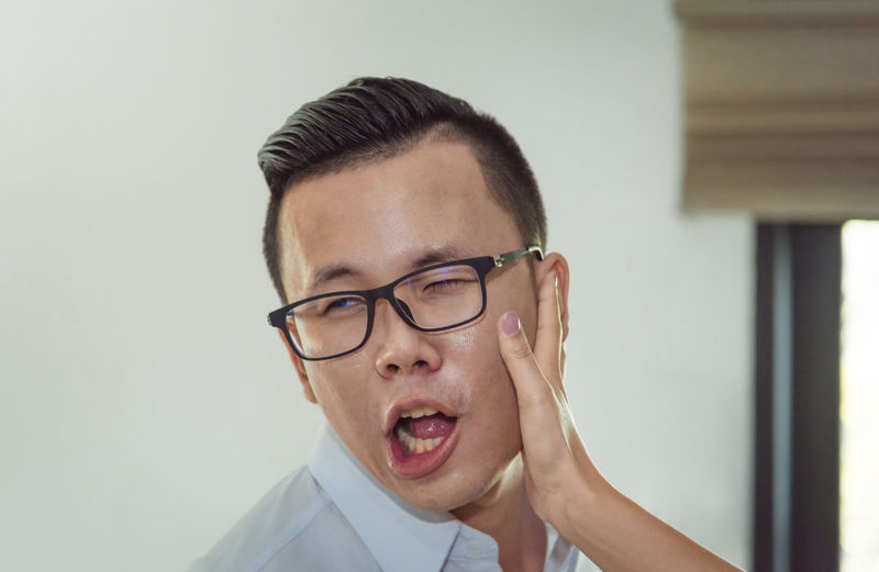 Cropped hand of woman slapping on face of man