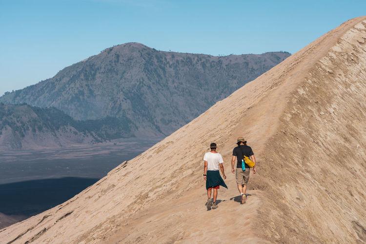 Rear view of friends walking on mountain road