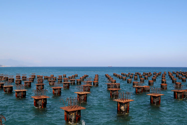 High angle view of metal structures in sea against sky