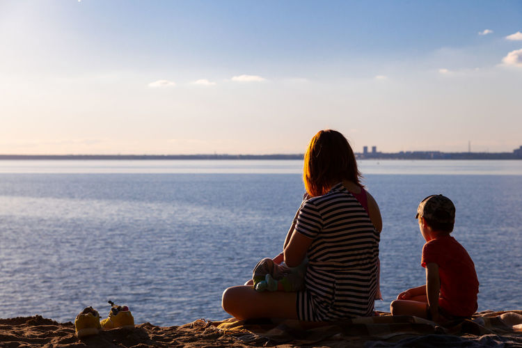 A young mother with her children boy and a newborn are sitting and enjoying the nature of the sea
