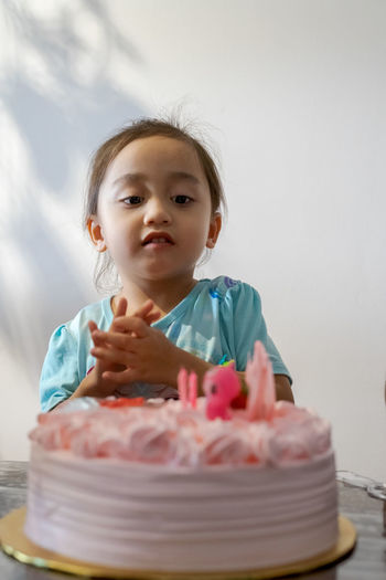 Portrait of girl by cake