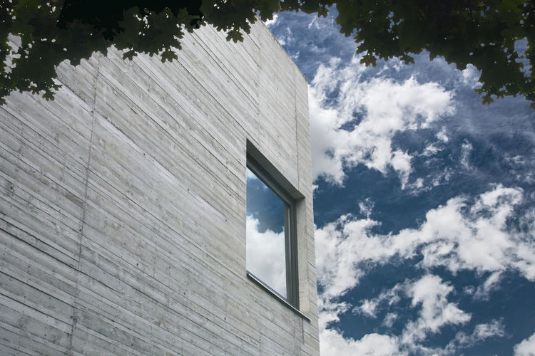 Contemporary building facade and sunny cloudy sky. Cloud - Sky Sky Architecture Built Structure Low Angle View Day Building Exterior Façade No People Building Outdoors Sunlight Contemporary Architecture Window Reflection Wall Concrete