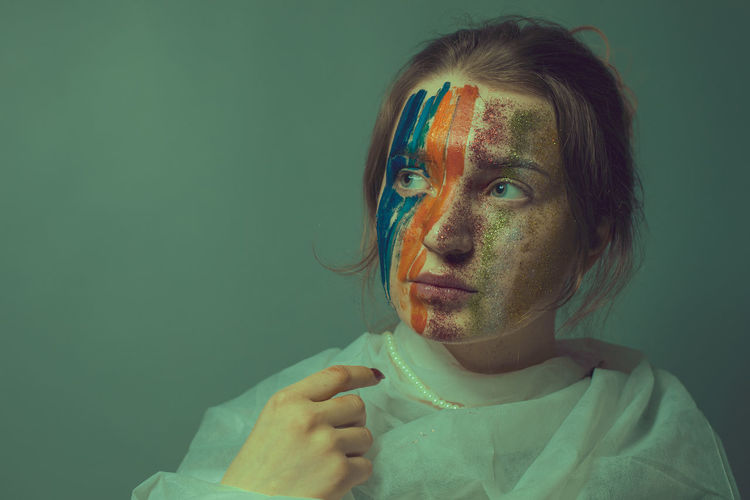 Young woman with painted face against green background
