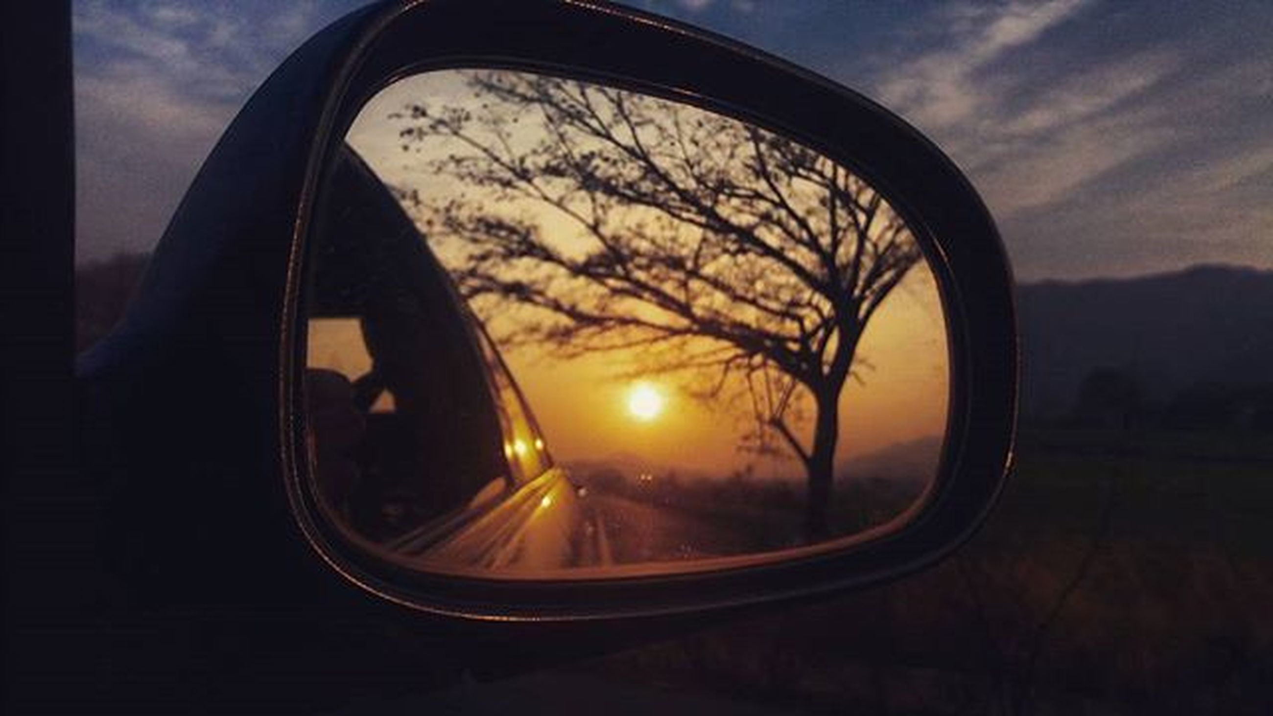 transportation, mode of transport, land vehicle, sunset, side-view mirror, sky, car, reflection, silhouette, cloud - sky, part of, travel, close-up, glass - material, vehicle interior, transparent, street, orange color, stationary, cloud