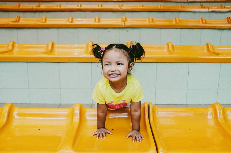High Angle View Of Cheerful Girl Leaning On Yellow Retaining Wall