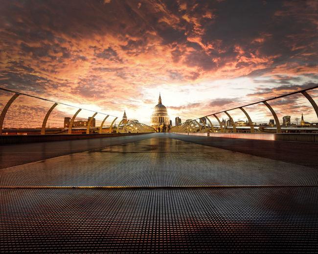 Footbridge against sky during sunset