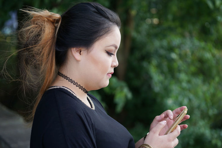 Side view of young woman using mobile