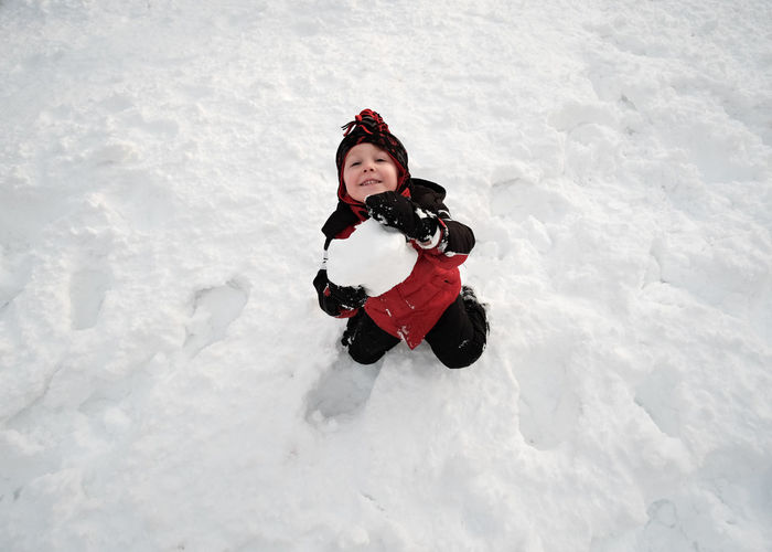 boy toddler playng in the snow , holding a giant snowball. Hat Toddler  White Snow Snowball Snowing Winter Wintertime Play Playing Boy Child Childhood Fun Snowday Young Winter Coat Mitten Snowball Glove Snowman Ski-wear Blizzard