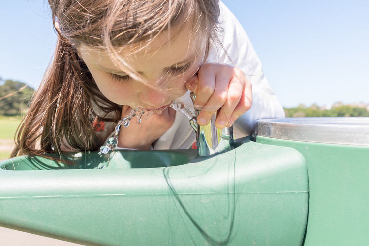 Close-up of girl drinking water from fountain in park during sunny day