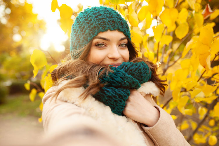 Portrait of beautiful young woman in warm clothing against autumn tree