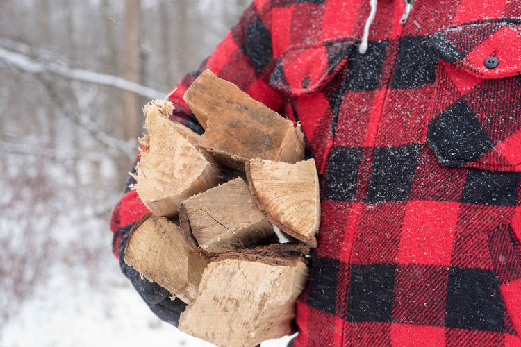 Midsection of man carrying logs on field during winter
